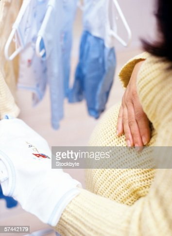 high angle close-up of a woman holding baby clothes and touching her pregnant stomach
