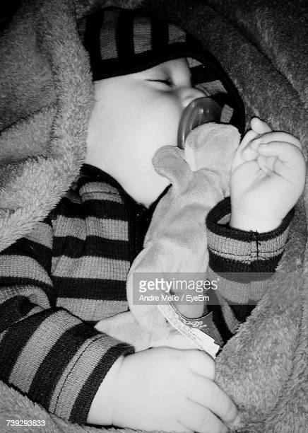High Angle Close-Up Of Baby With Pacifier In Mouth Sleeping On Bed At Home
