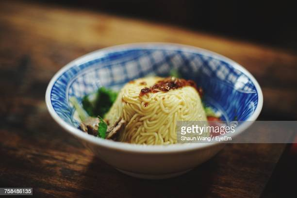 High Angle Close-Up Of Noodles Served In Bowl On Wooden Table