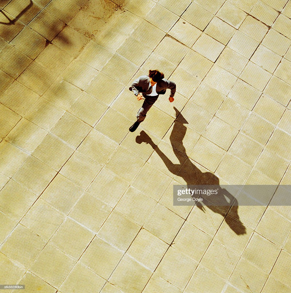 high angle of a businessman running in an open courtyard : Stock Photo