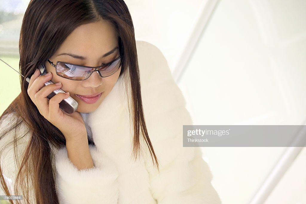 High angle of a woman wearing sunglasses and talking on her cell phone. : Stock Photo