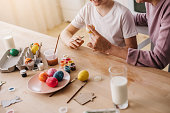 Cropped photo of grandson painting Easter egg while sitting at table. His grandmother is helping him to prepare for holiday, Family traditions concept