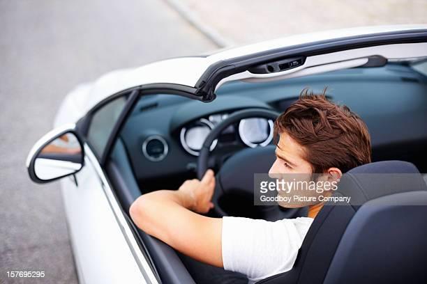 Alto angolo della splendida giovane uomo guida Auto convertibile in velocità