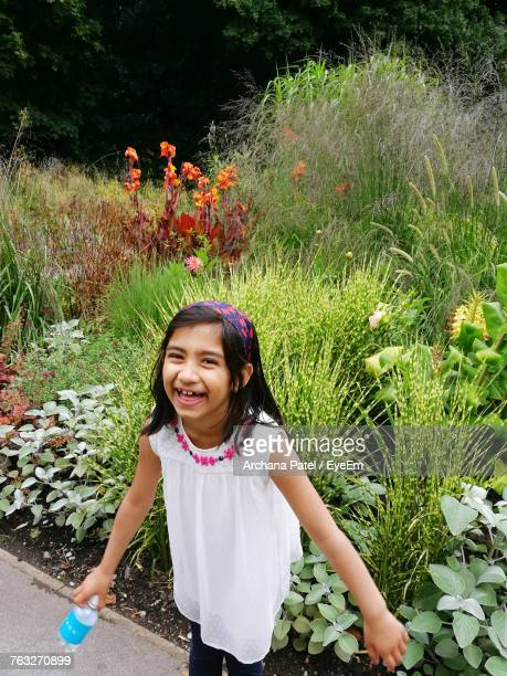 High Angle Portrait Of Cheerful Girl Standing Against Plants At Park