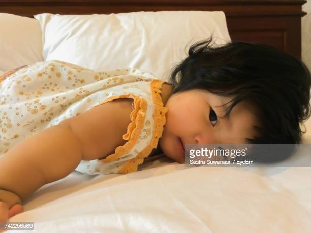 High Angle Portrait Of Cute Baby Girl Lying On Bed At Home