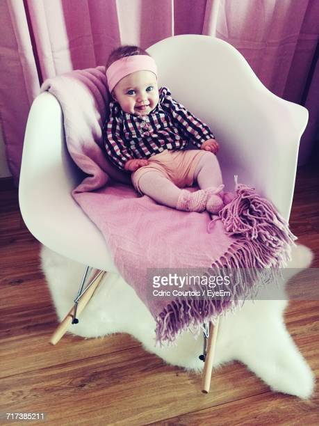 High Angle Portrait Of Cute Toddler Sitting On Chair At Home