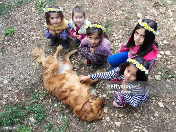 High Angle Portrait Of Girls Crouching By Golden Retriever Lying Ground