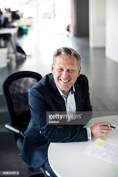 High angle portrait of happy mature businessman sitting at desk in office