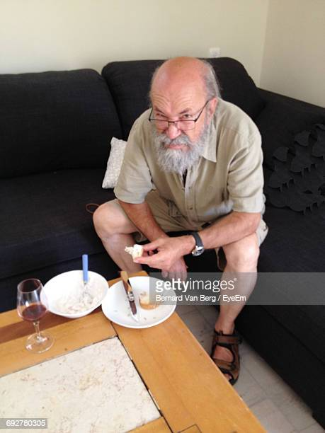 High Angle Portrait Of Mature Man Having Food On Sofa At Home