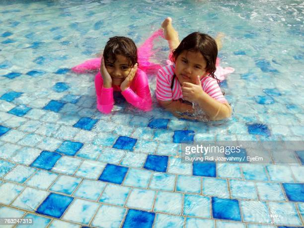 High Angle Portrait Of Sisters Lying In Swimming Pool