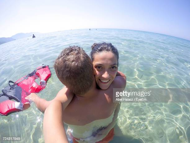 High Angle Portrait Of Smiling Couple In Sea