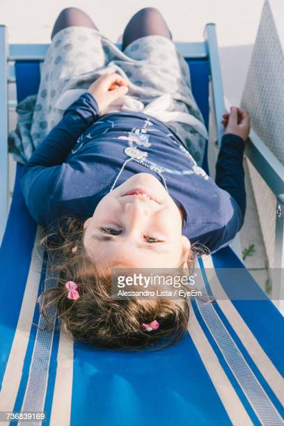 High Angle Portrait Of Smiling Girl Sitting Outdoors
