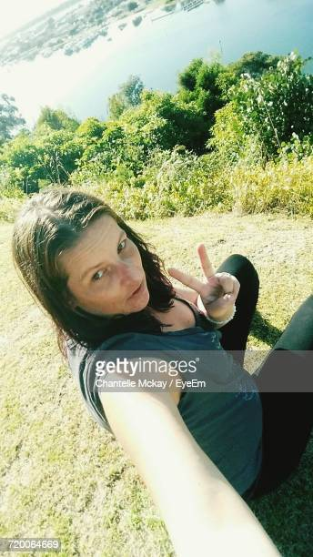High Angle Portrait Of Woman Gesturing Peace Sign While Sitting On Grassy Field