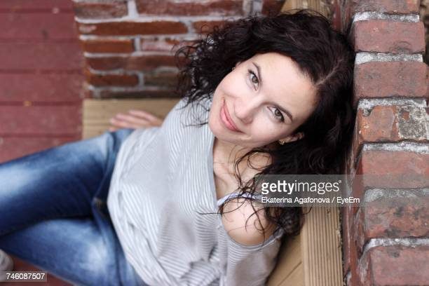 High Angle Portrait Of Woman Leaning On Brick Wall