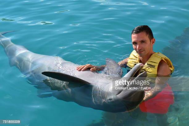 High Angle Portrait Of Young Man Holding Dolphin In Sea