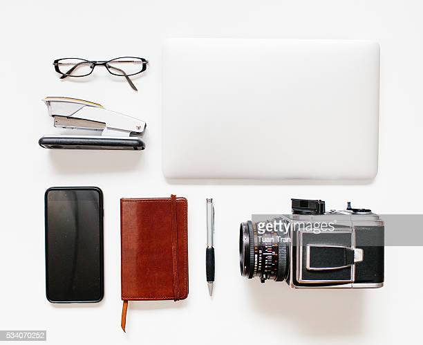 High angle shot of laptop, camera and cell phone on white background