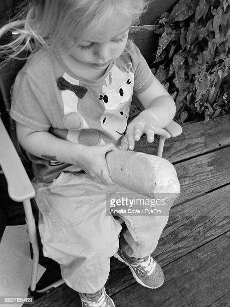 High Angle View Cute Girl Holding Bread While Sitting On Chair In Yard