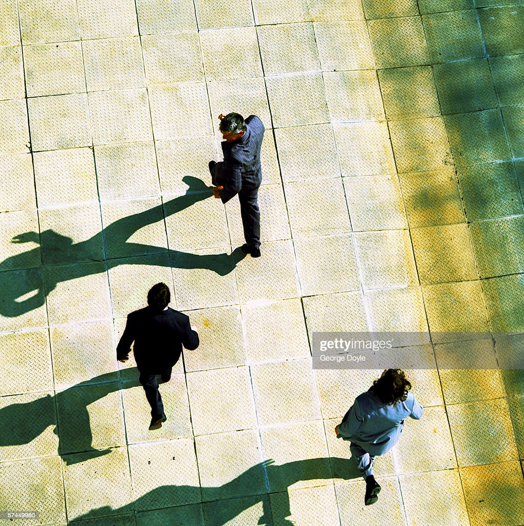 high angle view from behind of three businessmen running out of a building