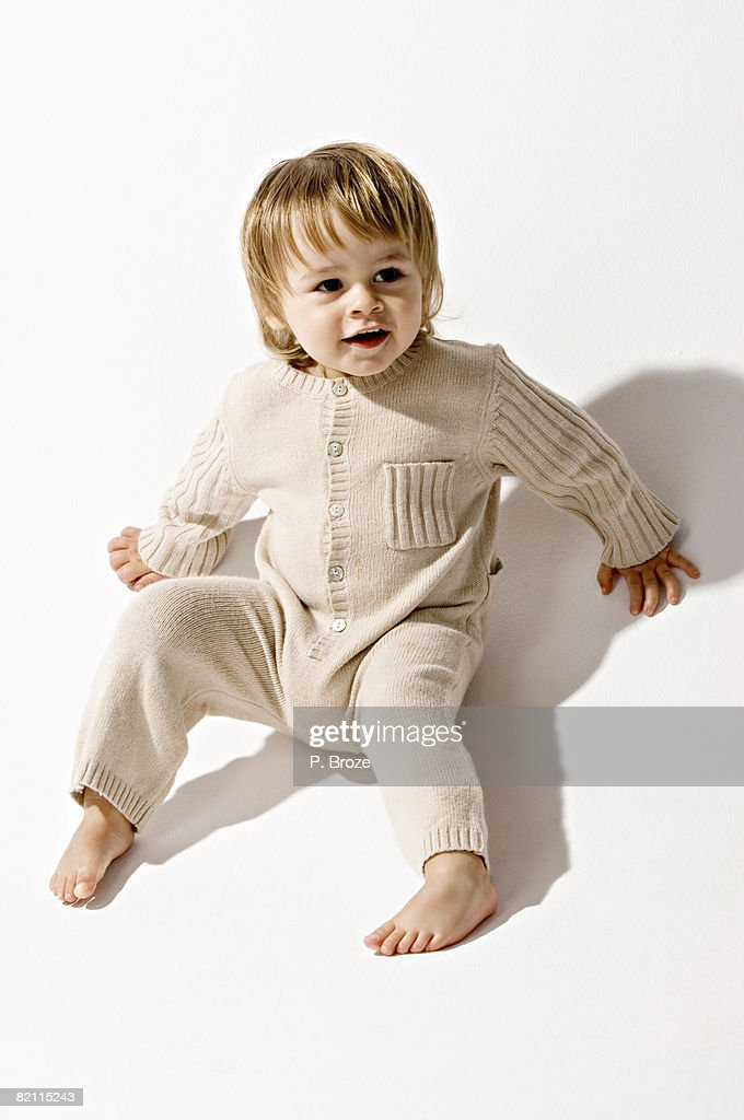 High angle view of a baby boy sitting on the floor and smiling : Stock Photo