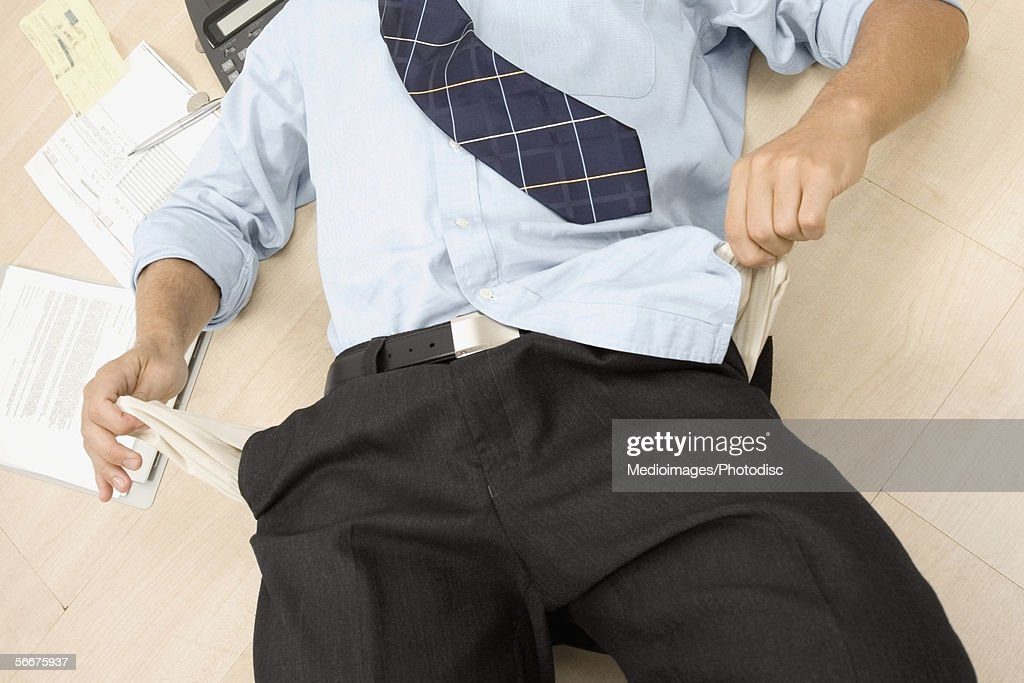 High angle view of a businessman showing his empty pockets : Stock Photo