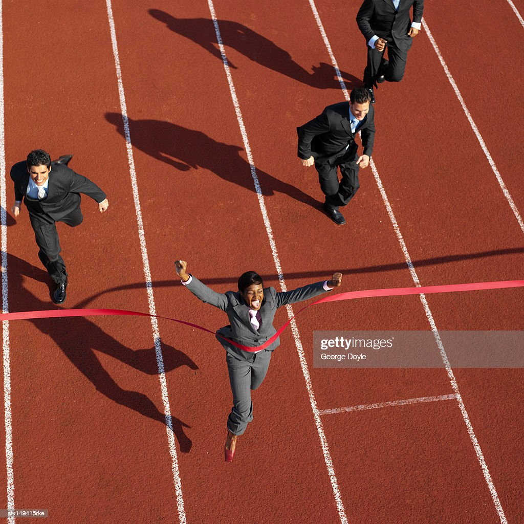 high angle view of a businesswoman crossing the finish line ahead of businessmen : Stock Photo