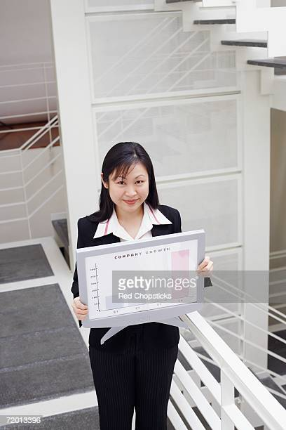 High angle view of a businesswoman holding a computer model showing progress report