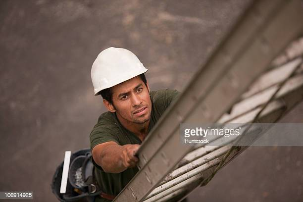 High angle view of a carpenter climbing a ladder at a construction site