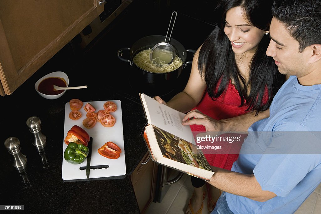 High angle view of a couple preparing food with the help of a cookbook in the kitchen : Stock Photo