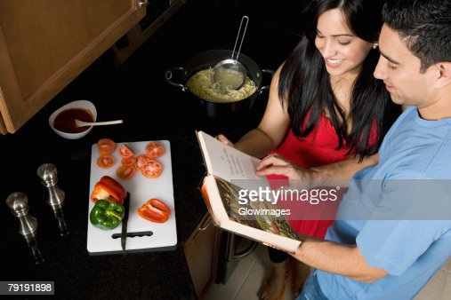High angle view of a couple preparing food with the help of a cookbook in the kitchen : Foto de stock