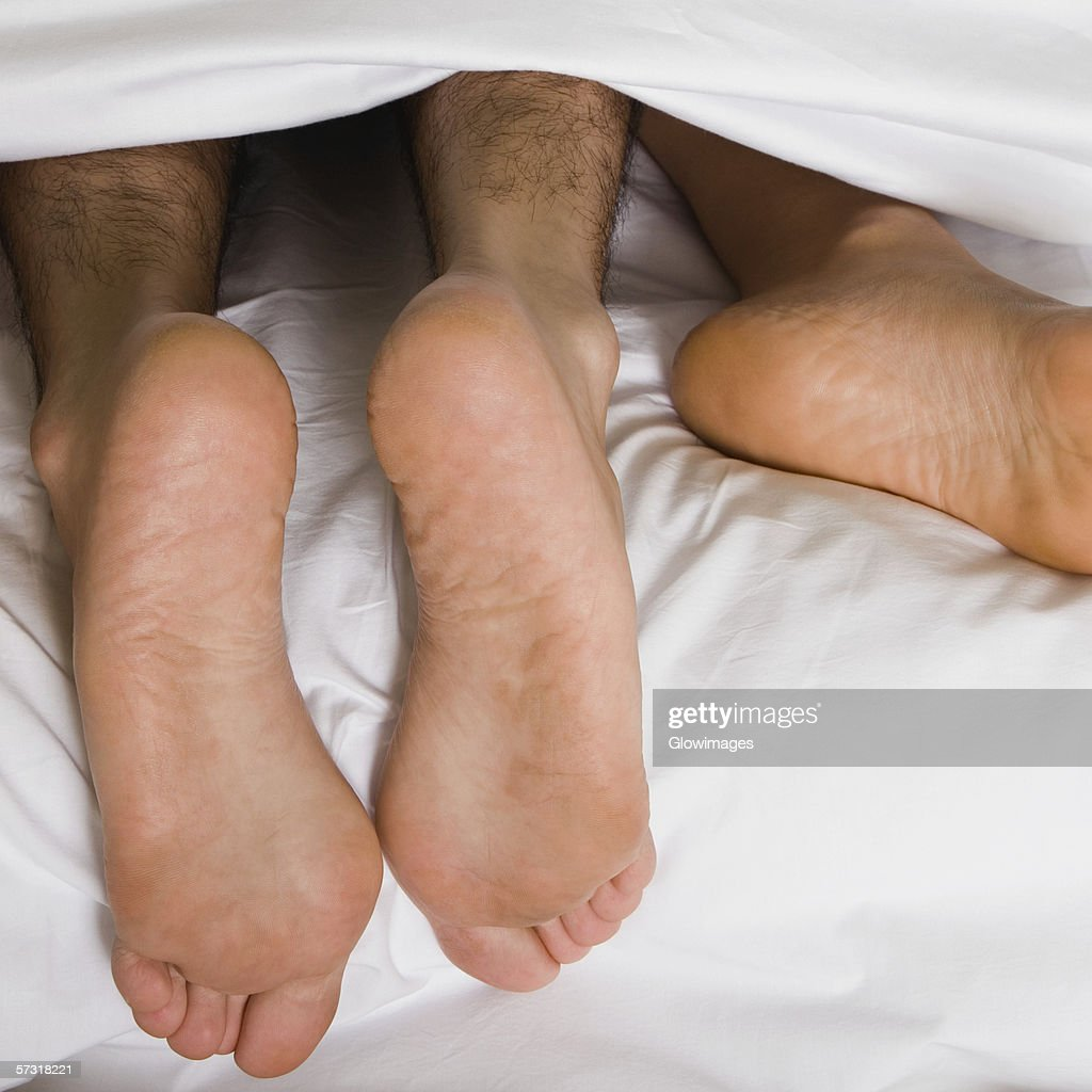 High angle view of a couple's feet under the sheets of a bed : Stock Photo
