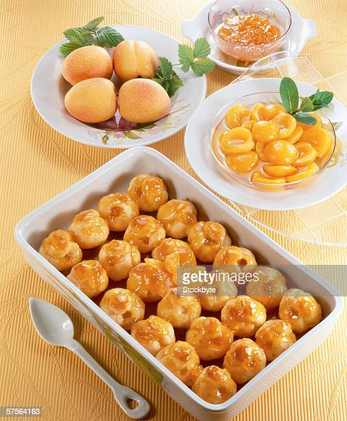 high angle view of a dish of baked glazed peaches served on a table with whole peaches and candied peaches