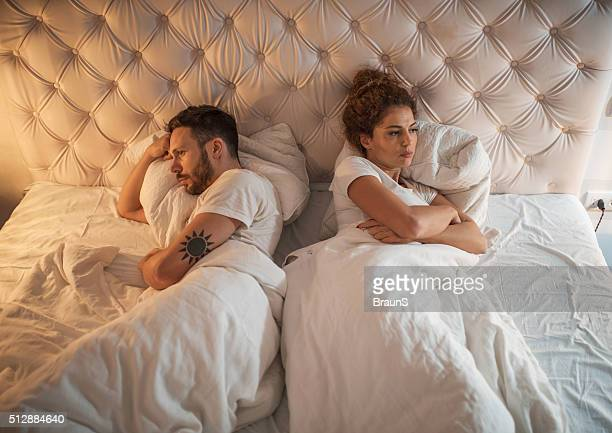 High angle view of a displeased couple in bed.