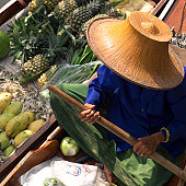 High angle view of a female vendor sitting in a boat selling fruit, Bangkok, Thailand