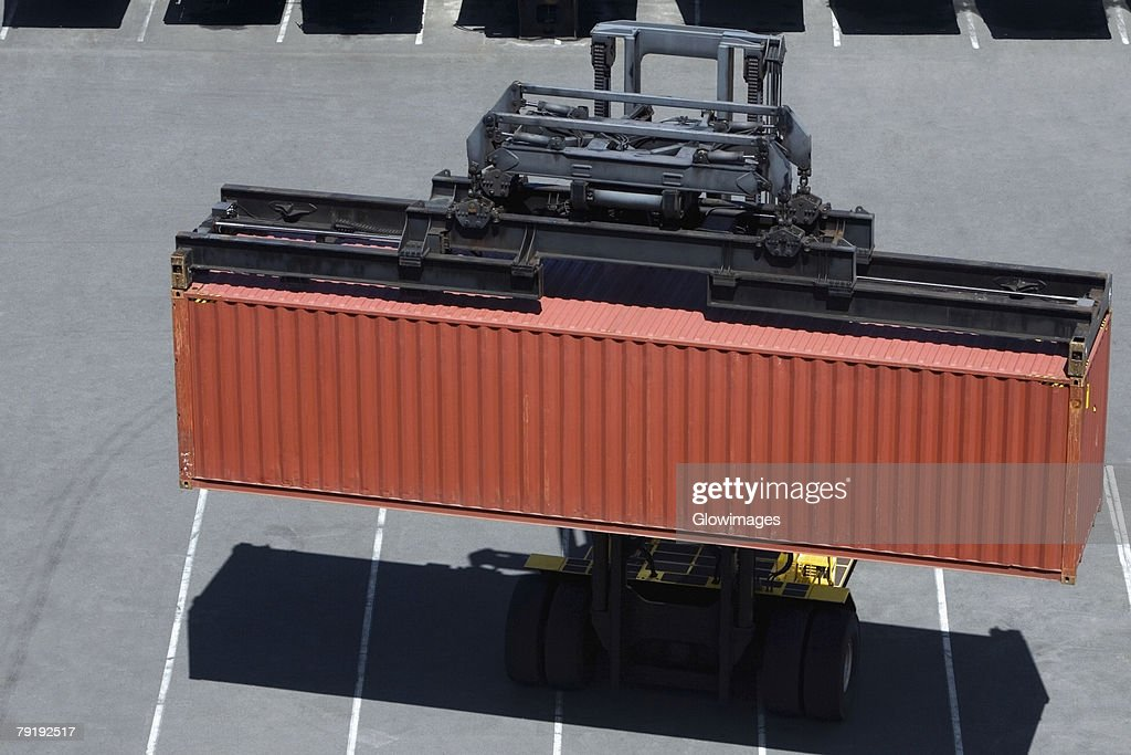 High angle view of a forklift picking up a cargo container at a commercial dock : Foto de stock