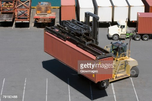 High angle view of a forklift picking up a container at a harbor : Foto de stock