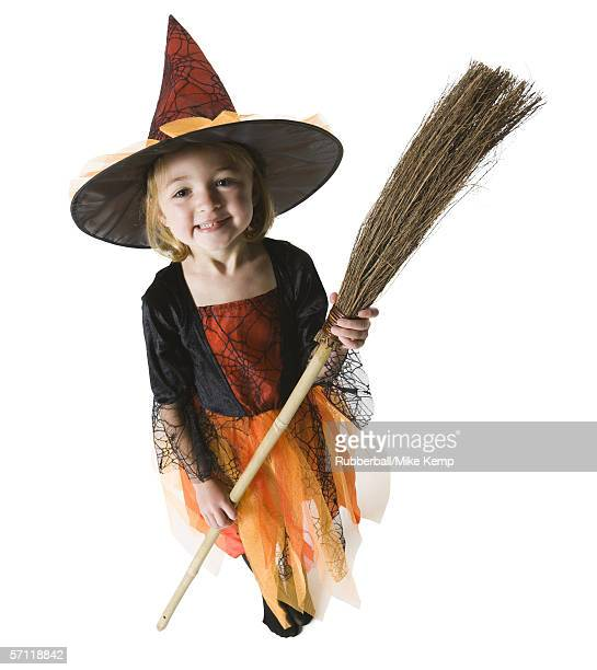 High angle view of a girl dressed as a witch holding a broom