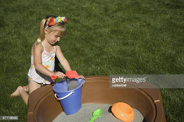 High angle view of a girl playing with sand