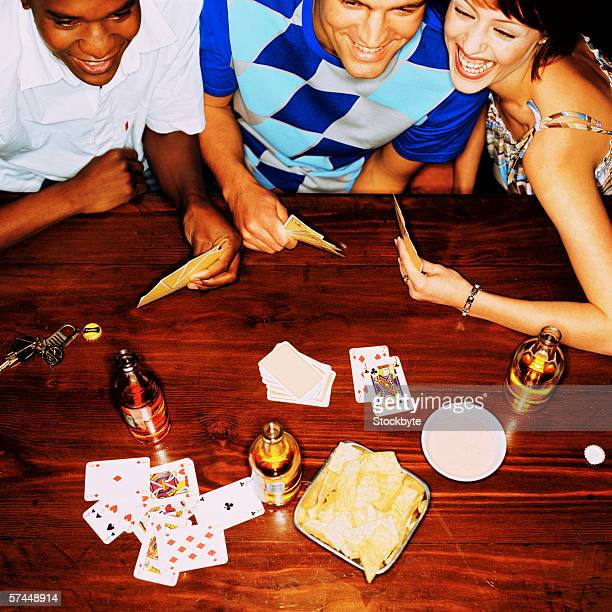 high angle view of a group of friends playing cards and drinking beer at a table