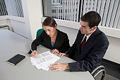 High angle view of a handicapped businessman and a businesswoman working in an office