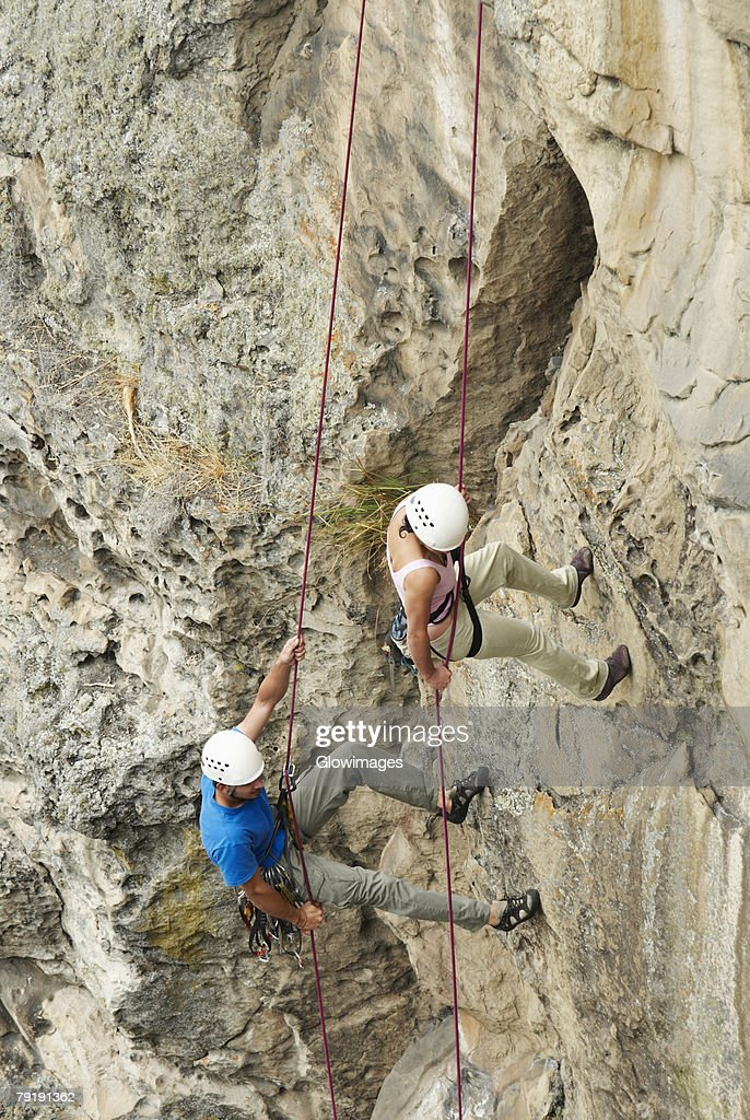 High angle view of a male and a female rock climber scaling a rock face : Foto de stock
