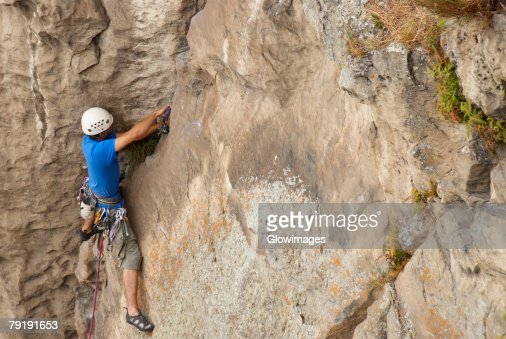 High angle view of a male rock climber hinging a rope on a rock : Foto de stock