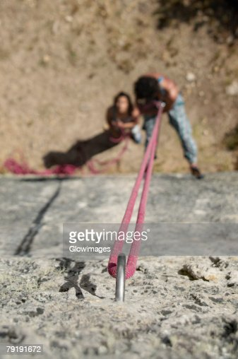 High angle view of a male rock climber scaling a rock with a female rock climber looking at him : Foto de stock