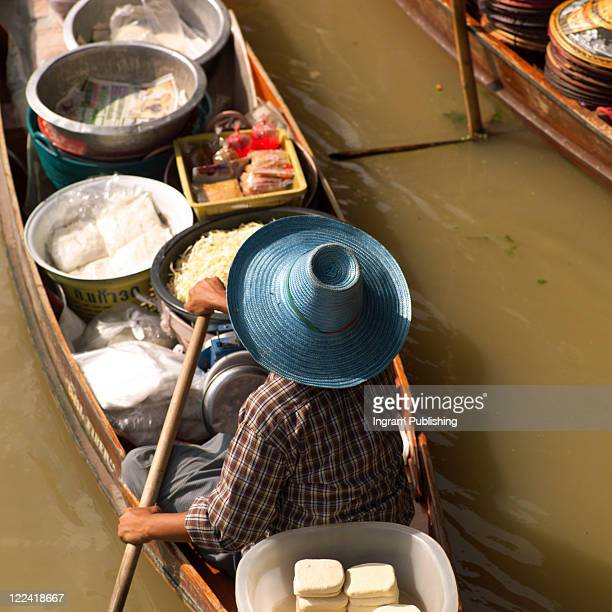 High angle view of a male vendor sitting in a boat selling food, Bangkok, Thailand