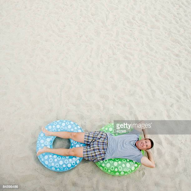 High angle view of a mature man lying on inflatable rings