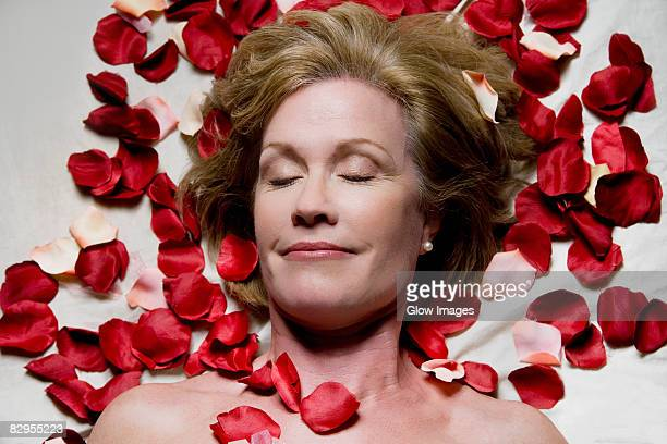 High angle view of a mature woman lying on a massage table with rose petals around her