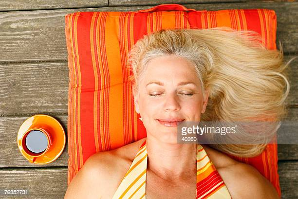 High angle view of a mature woman lying on her back with her eyes closed