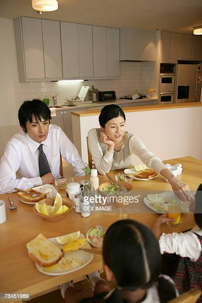High angle view of a mid adult couple and their daughters at the dining table