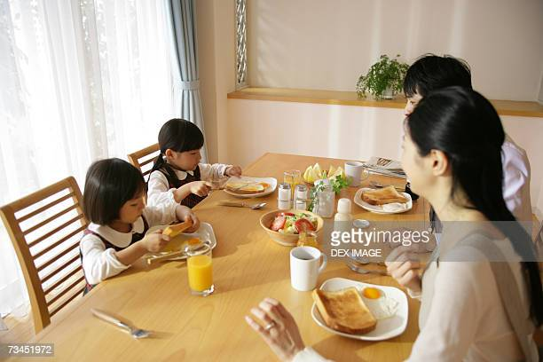 High angle view of a mid adult couple and their daughters sitting at the dining table