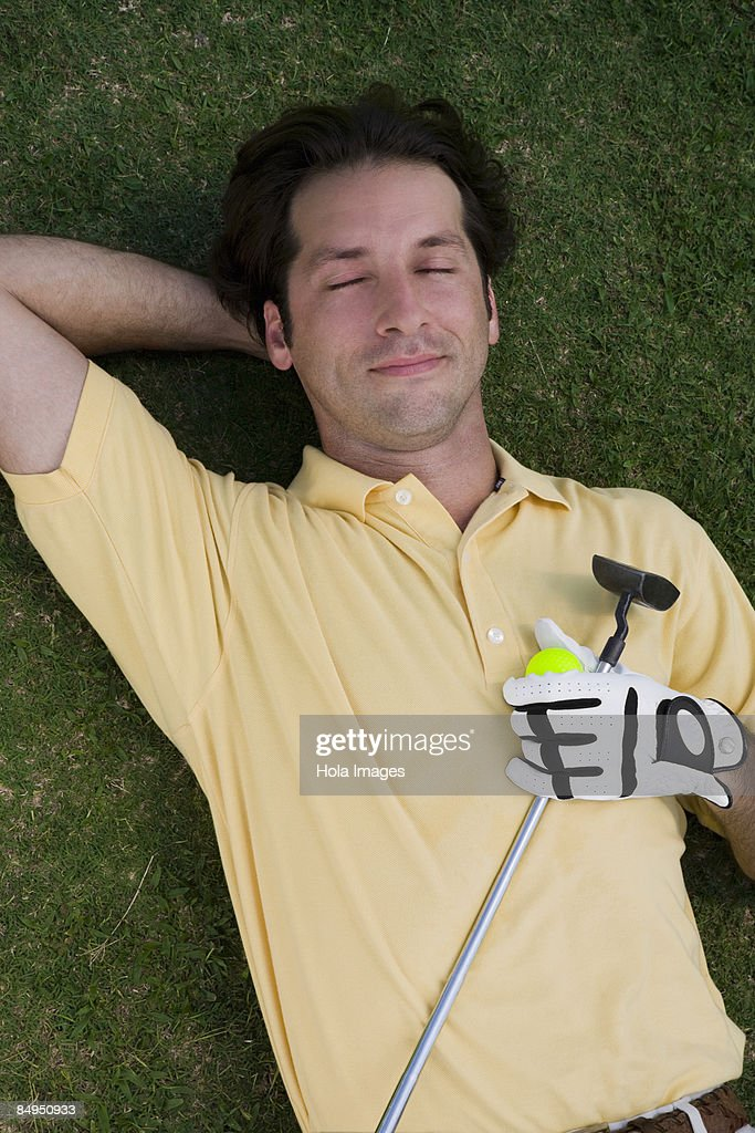High angle view of a mid adult man lying on a golf course with a golf ball and a golf club : Stock Photo