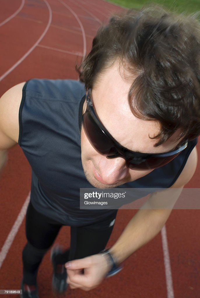 High angle view of a mid adult man running on a running track : Stock Photo